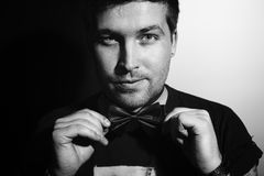 Young man in a bow tie with a sly smirk. Portrait of a young man in a bow tie with a sly smirk on his face stock photography