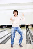 The young man in bowling. The joyful young man plays bowling Stock Images