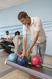 Young Man At Bowling Alley Choosing Ball Royalty Free Stock Photo