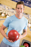 Young man a in bowling ally. Young man holding a bowling ball in a bowling ally Royalty Free Stock Images