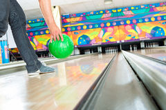 Young man bowling having fun. Young man in bowling alley having fun, the sporty man playing a bowling ball in front of the tenpin alley Stock Photography