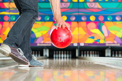 Young man bowling having fun. Young man in bowling alley having fun, the sporty man holding a bowling ball in front of the ten pin alley Royalty Free Stock Photos