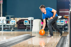 Young man bowling having fun. Young man in bowling alley having fun, the sporty man playing a bowling ball in front of the tenpin alley Royalty Free Stock Photography