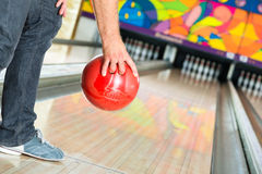 Young man bowling having fun. Young man in bowling alley having fun, the sporty man holding a bowling ball in front of the ten pin alley Royalty Free Stock Image