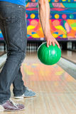 Young man bowling having fun. Young man in bowling alley having fun, the sporty man holding a bowling ball in front of the ten pin alley Stock Image