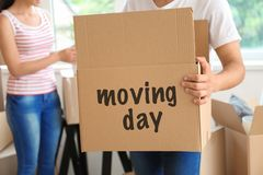 Young man with box indoors. Moving into new house royalty free stock image