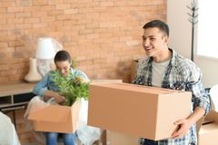 Young man with box indoors. Moving into new house. Young men with box indoors. Moving into new house royalty free stock photos