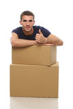 A young man with a box shows the finger to the top Stock Image