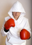 Young man with boxing gloves on. Young man in a hood Royalty Free Stock Images