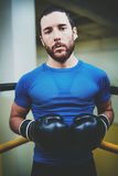 Young man boxing workout on ring in a fitness club. Caucasian male boxer in black gloves. Muscular strong man on Stock Photos