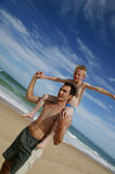 Young man and boy at the beach. Dad carrying his son on his shoulders on the beach Royalty Free Stock Images