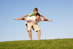 Young man with boy playing in a field Royalty Free Stock Images