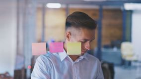 Young man brainstorming ideas working in modern glass office. Handsome Businessmanstick a sticky note on glass board stock video