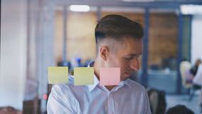 Young man brainstorming ideas working in modern glass office. Handsome Businessmanstick a sticky note on glass board stock footage