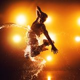 Young man dancing. Young man break dancer with lights and water effects. Tattoo on hand Stock Photos