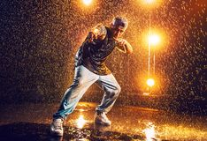 Young man dancing. Young man break dancer standing in club with lights and water. Tattoo on body Stock Photos