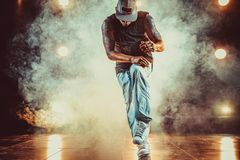 Young man break dancer. Young cool man break dancing in club with lights and smoke. Tattoo on body Royalty Free Stock Photos