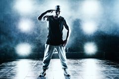 Young man break dancer. Standing in club with lights and smoke. Tattoo on body. Blue tint colors Stock Photos