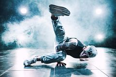 Young man dancing. Young man break dancing in club with lights and smoke. Tattoo on body. Blue tint colors Royalty Free Stock Photo