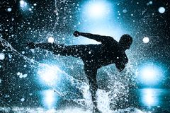 Young man dancing. Young man break dancing in club with lights and water. Blue tint colors and dramatic silhouette Stock Photo