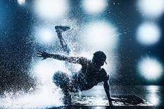 Young man dancing. Young man break dancing in club with lights and water. Tattoo on body. Blue tint colors Royalty Free Stock Photos
