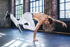 Young man break dancing. In old sunny urban interior stock photos