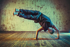 Young man break dancing. On wall background. Blue and yellow vibrant colors tint royalty free stock image