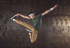 Break Dance. Young man break dancing on the wall background, performing tricks stock images