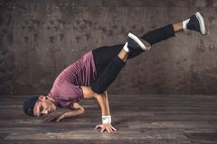 Break Dance. Young man break dancing on the wall background, performing tricks stock photo