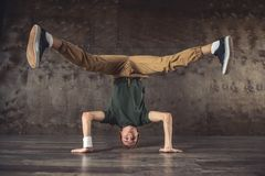 Break Dance. Young man break dancing on the wall background, performing tricks royalty free stock images
