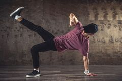 Break Dance. Young man break dancing on the wall background, performing tricks royalty free stock photo