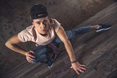 Break Dance. Young man break dancing on the wall background, performing tricks royalty free stock image