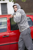Young Man Breaking Into Car Royalty Free Stock Photography