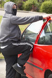Young Man Breaking Into Car Royalty Free Stock Images