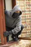 Young Man Breaking Into House Stock Photography