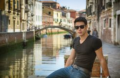 Young Man on Bridge Over Narrow Canal in Venice Stock Image