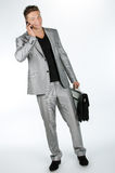 Young man with briefcase and cell phone Royalty Free Stock Images