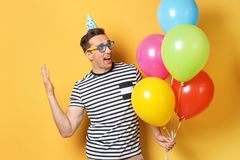 Young man with bright balloons on color background. Birthday celebration stock photography