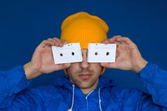 Man in a bright blue jacket and yellow hat holding vintage audio cassettes on a bright blue background. Young man in a bright blue jacket and yellow hat holding stock photos