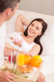 Young man bringing breakfast in bed. Royalty Free Stock Photo