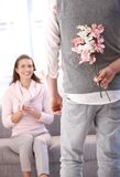Young man bringing flowers to woman stock photo