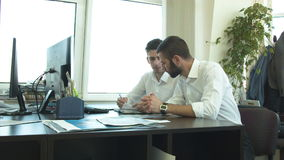 A young man brings a colleague to the development of a business plan stock video