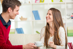A young man brings his girlfriend coffee Stock Photos