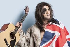 Young man with British flag holding guitar against light blue background Stock Image
