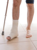 Young man with a broken ankle and a leg cast. Young man with a broken ankle and a white cast on his leg, walking on crutches ( on white stock photos