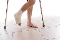 Young man with a broken ankle and a leg cast. Young man with a broken ankle and a white cast on his leg, walking on crutches ( on white stock image