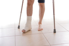 Young man with a broken ankle and a leg cast. Young man with a broken ankle and a white cast on his leg, walking on crutches ( on white royalty free stock photo