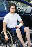 Young man with broken arm in hospital lot. Young man with plaster cast after an accident in wheelchair arriving or leaving the hospital, car with opened door in Stock Photo