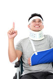 Young man with broken arm pointing upwards Royalty Free Stock Photography