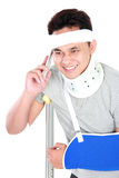 Young man with broken arm talking on the phone Stock Images